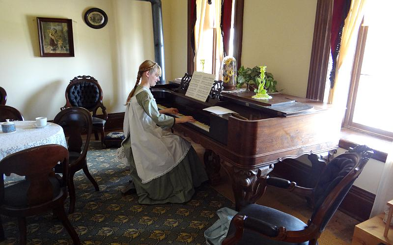 girl playing the piano in historical costume